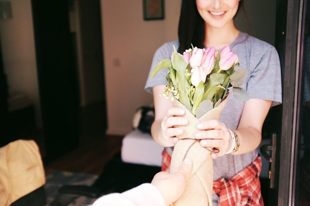 Frau bekommt einen Tulpenstrauß als Geschenk überreicht
