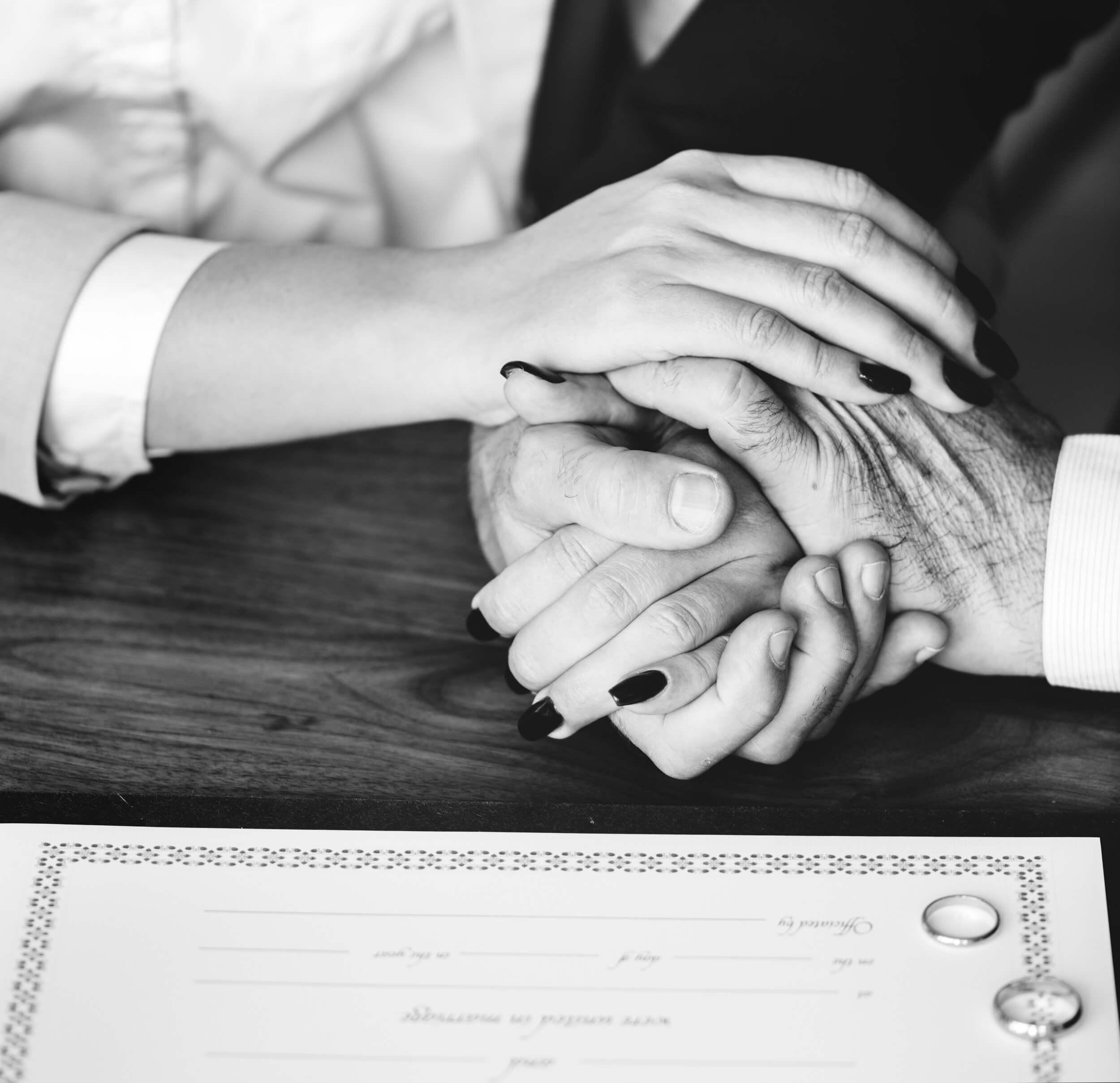 Frau und Mann halten sich fürsorglich an den Händen