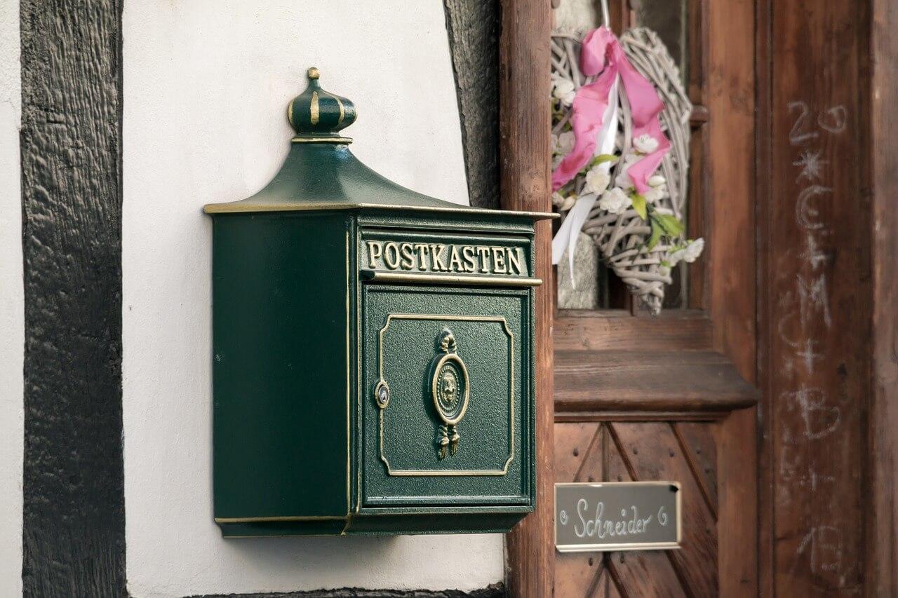 altmodischer grüner Briefkasten hängt an der Hauswand