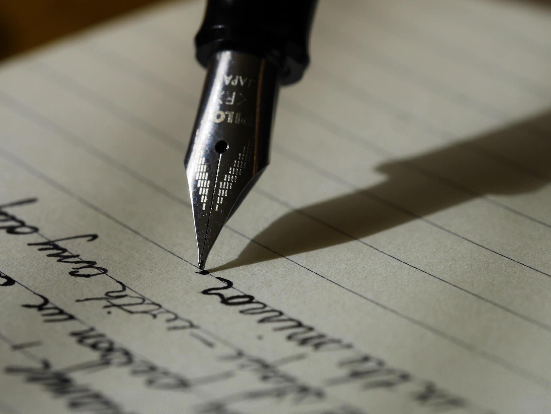 Mit einem Füller auf Papier schreiben