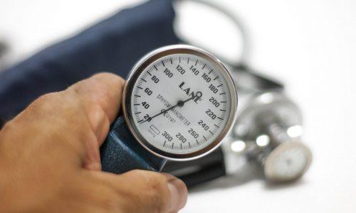 Blutdruckmessgerät wird von einer Hand ins Bild gehalten