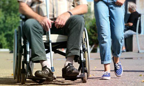 Mann im Rollstuhl mit Stock und laufender Person daneben